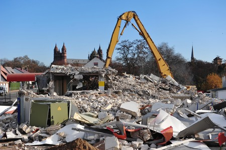 house demolition: Demolition of a house with yellow construction machine Stock Photo