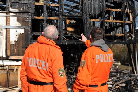 observe: Police officers observe destroyed home