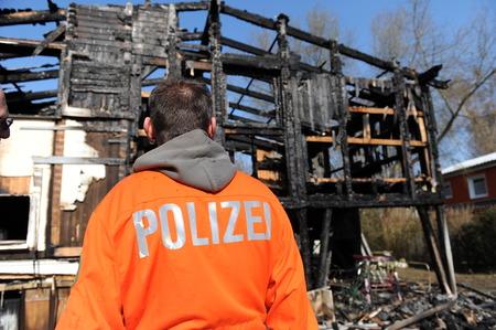 observes: Police officer observes destroyed home Stock Photo
