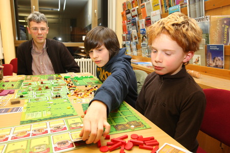 Frankfurt, Germany - Februar 20, 2009 - Father playing a board game with his children on World Game Day