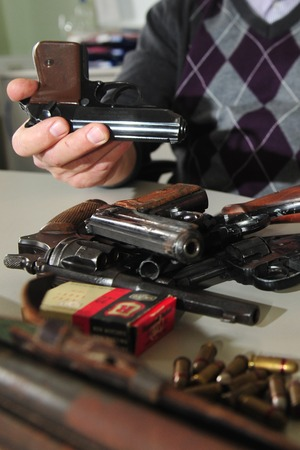 Worms, Germany - November 26, 2009 - Officer shows guns and ammunition confiscated during a raid