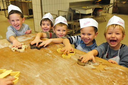 galletas de jengibre: Hamburgo, Alemania - 24 de noviembre de 2009: los ni�os de kindergarten hornear galletas de Navidad como parte de la educaci�n en grupo Editorial