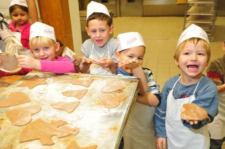 Hamburg, Germany - November 24, 2009: Kindergarten kids baking christmas cookies as part of group education