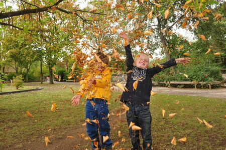 financial problems: Worms, Germany - October 7, 2009: Children playing with leaves in fall in a public park, which is threatened to be closed because financial problems of municipality