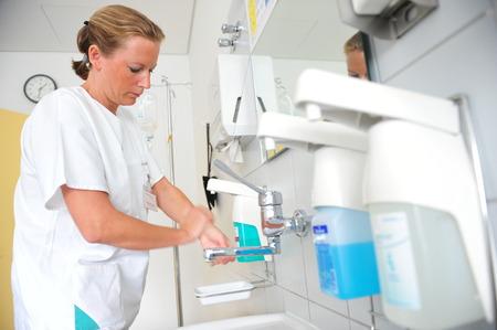 프랑크푸르트, 독일 -2009 년 9 월 17 일 - 감염을 피하기 위해 병원에서 손을 씻는 의사 에디토리얼