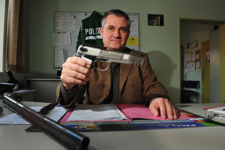 raid: Worms, Germany - November 26, 2009 - Officer shows guns and ammunition confiscated during a raid