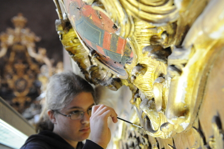 Worms, Germany - May 6, 2009 - Women restores ornaments in cathedral  of Worms and adds gold leafs