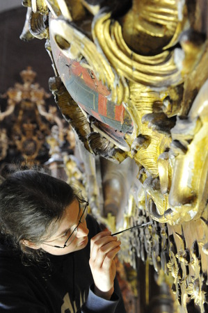 adds: Worms, Germany - May 6, 2009 - Women restores ornaments in cathedral  of Worms and adds gold leafs