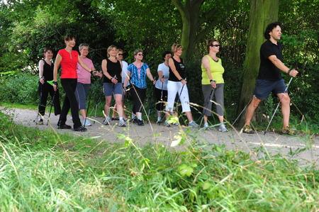 Munich, Alemania - 21 de julio de 2009: Gente que hace nordic walking con entrenadores patrocinados por los seguros de salud alemán para apoyar la vida activa