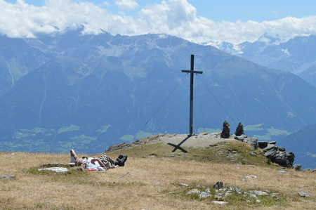 lonesome: Vinschgau, Italy - July 31, 2015: Lonesome climber takes break on top of mountain Spitzige Lun near Matsch in South Tryol towards Etschtal, Vinschgau and Ortler
