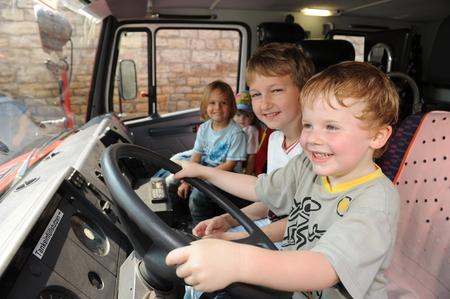 incendio casa: Frankfurt, Alemania - 2 de mayo de 2009 - Los niños sentado en un camión de bomberos en un día de puertas abiertas jugando figthers fuego Editorial