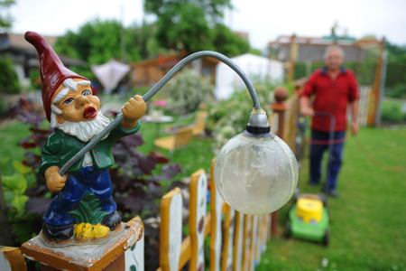 Garden gnome in german garden with men mowing lawn