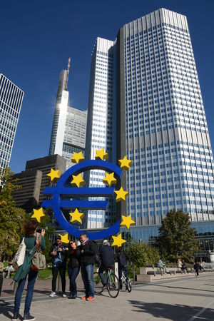 bce: Frankfurt, Germany - October 1, 2015 - Tourist taking pictures in front of Euro Tower with euro sculpture during finance and refugee crises in Europe