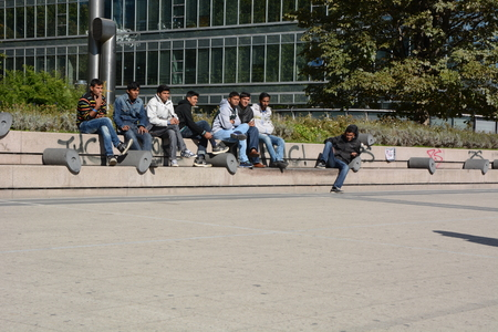 bce: Frankfurt, Germany - October 1, 2015 - Young male refugees hanging around in front of Euro Tower in the financial heart of Europe