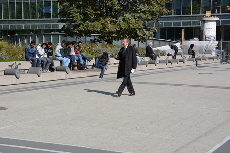 bce: Frankfurt, Germany - October 1, 2015 - Young male refugees hanging around in front of Euro Tower in the financial heart of Europe, business man walking by