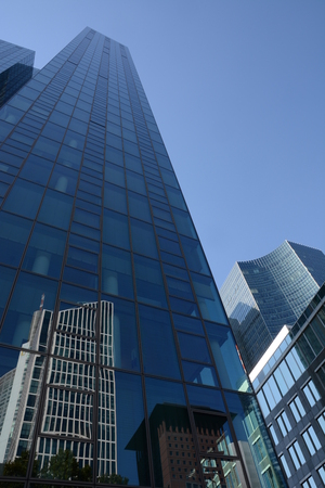 finacial: Frankfurt, Germany - October 1, 2015 - skyscraper with reflections of Commerzbank Tower and parts of finacial discrict