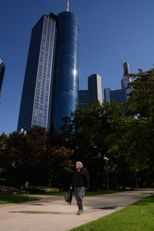 1 person: Frankfurt, Germany - October 1, 2015 - Main Tower and Commerzbank Tower seen from Taunusanlage with person walking by Editorial