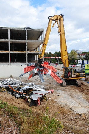 disassemble: Worms, Germany - November 25, 2009: Demolition of an industrial building with yellow construction machine and cathedral of Worms in background