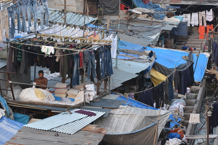 dhobi ghat: Mumbai, India - October 19, 2015 - Muslim washing spot Dhobi Ghat in front of Mumbai skyline. Man folding clothes Editorial