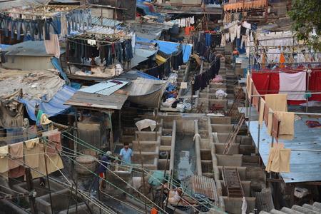 dhobi ghat: Mumbai, India - October 19, 2015 - Muslim washing spot Dhobi Ghat in front of Mumbai skyline