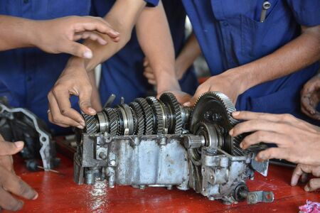 mechanician: Mumbai, India - October 26, 2015 - Teenager from children«s doing training to become a car mechanician in education center powered by european charity organisation fixing a transmission