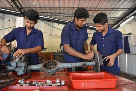 mechanician: Mumbai, India - October 26, 2015 - Teenager from children«s doing training to become a car mechanician in education center powered by european charity organisation fixing an axis