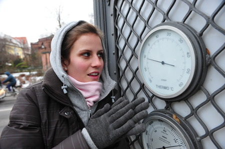 very cold: Munich, Germany - January 6, 2010 - Girl freezing in very cold winter looking at thermometer during minus degree record in Germany Editorial