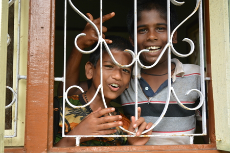 Mumbai, India - October 27, 2015 - Kids looking out of window of childrens home build with money from european charity project