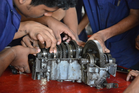 mechanician: Mumbai, India - October 26, 2015 - Teenager from children�s doing training to become a car mechanician in education center powered by european charity organisation fixing a transmission