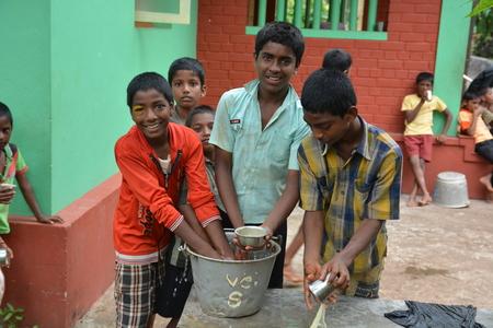 unicef: Mumbai, India - 27 Ottobre 2015 - Bambini da Childrens Home potabile piatti di acqua e lavaggio di nuovo ben alimentati dalla carit� da Europa