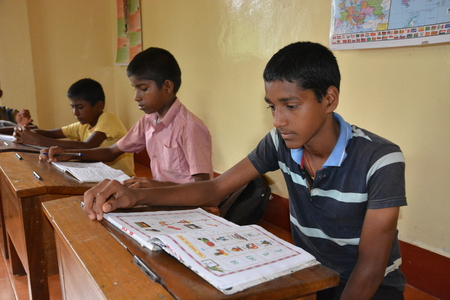 Mumbai, India - October 27, 2015 - Children from children«s home learning and studying powered by chartiy project based in Europe, reading in books, writing and drawing Editorial