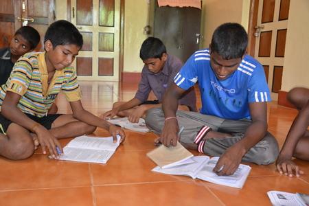 unicef: Mumbai, India - 27 Ottobre 2015 - Bambini da apprendimento dei bambini a casa e lo studio alimentato da progetto chartiy con sede in Europa, la lettura di libri, la scrittura e il disegno Editoriali
