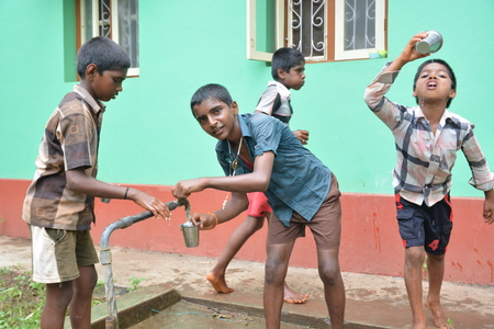 Mumbai, India - October 27, 2015 - Children from children«s home drinking water from new well powered by charity from europe Editorial