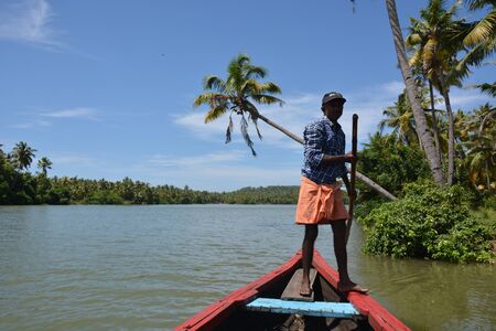 punt: Kerala, India - November 3, 2015 - Man on punt shipping tourists through indian backwaters Editorial