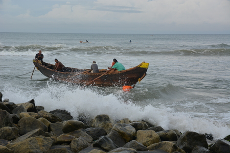 bargaining: Goa, India - November 5, 2015 - Fishermen catching fishes the traditional way  sharing the catch and bargaining. Pushing their boat into the water
