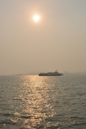 particulate: Mumbai, India - October 18, 2015 - Smog pollution in Mumbai, India seen from sea during sunset