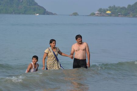 downshift: Palolem, India - October 21, 2015 - Tourists from India and allover the world walking and swimming at the beach of Palolem, Goa.