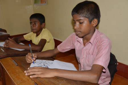 Mumbai, India - October 27, 2015 - Children from children´s home learning and studying powered by chartiy project based in Europe, reading in books, writing and drawing