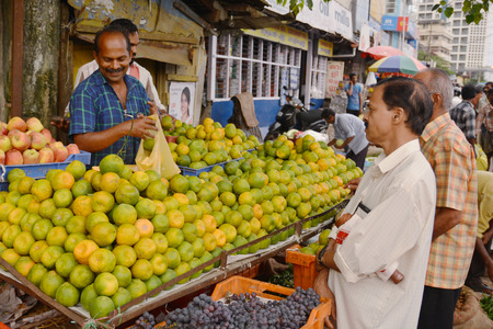 bargaining: Mumbai, India - November 6, 2015 - Vegetable traders on indian crawford market bargaining with clients