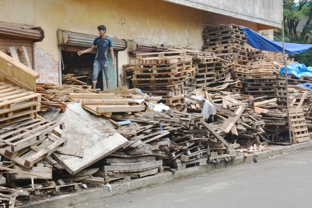 recycles: Kochi, India - November 7, 2015 - Indian boy working in company that recycles pallets