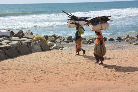 women's issues: Mumbai, India - November 3, 2015 - Woman carrying wood on beach in Goa