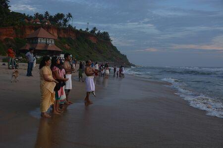 Varkala, India - November 5, 2015 - People and pilgrims praying at holy beach Varkala in Kerala, South India and taking a bath in the holy water