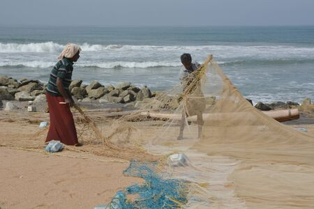 varkala: Goa, India - November 4, 2015 - Fishermen catching fishes the traditional way and repairing their huge nets Editorial