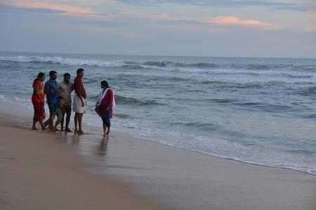 personas tomando agua: Varkala, India - 5 de noviembre el a�o 2015 - Las personas y peregrinos rezando en santa Varkala playa en Kerala, sur de la India y de tomar un ba�o en el agua bendita Editorial