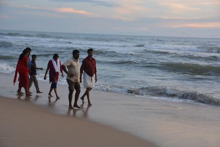 personas tomando agua: Varkala, India - 5 de noviembre el año 2015 - Las personas y peregrinos rezando en santa Varkala playa en Kerala, sur de la India y de tomar un baño en el agua bendita Editorial