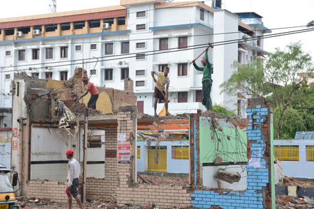 deconstruction: Mumbai, India - November 1, 2015 - Indian workers destroying house with hammers Editorial
