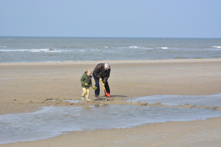 nine years old: Bergen aan Zee, Netherlands - March 26, 2016: Grandfather playing with grandchild on beach