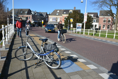 dutch typical: Alkmaar, Netherlands - March 27, 2016: People cycling on road Editorial