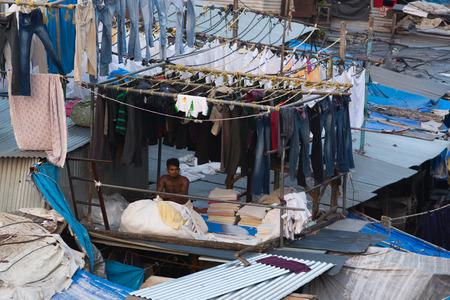 Mumbai, India - December 11, 2016 - Muslim washing spot Dhobi Ghat in front of Mumbai skyline. Man folding clothes Editorial