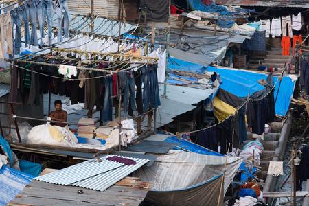 dhobi ghat: Mumbai, India - December 11, 2016 - Muslim washing spot Dhobi Ghat in front of Mumbai skyline. Man folding clothes Editorial
